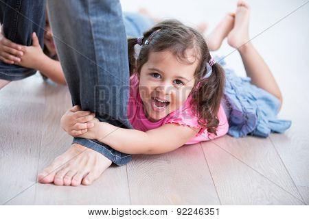 Portrait of playful girl with sister holding father's legs on hardwood floor