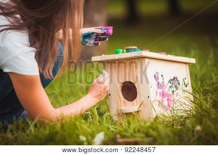 Girl painting birdhouse