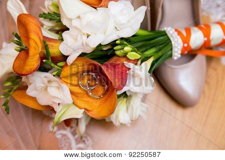 wedding rings with bouquet and shoes