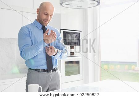 Mid adult businessman buttoning sleeve at home