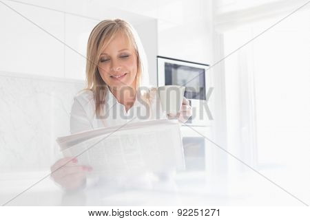 Happy mid adult businesswoman having coffee while reading newspaper at home
