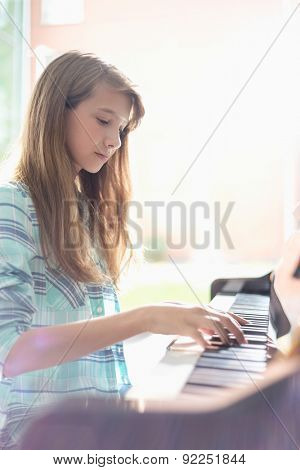 Side view of girl playing piano at home