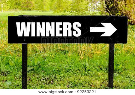 Winners Written On Directional Black Metal Sign