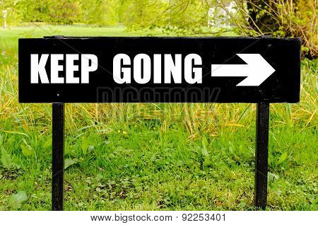 Keep Going Written On Directional Black Metal Sign