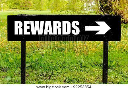 Rewards Written On Directional Black Metal Sign