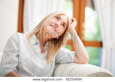 Pensive mature woman portrait relaxing on her sofa
