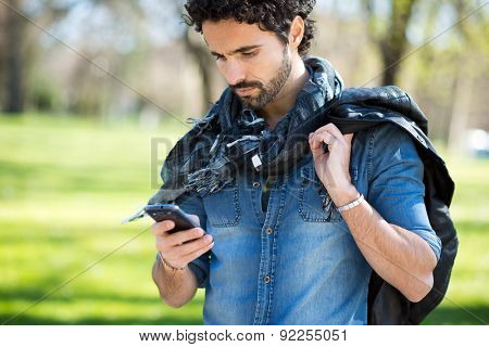 Portrait of a man using his mobile phone in a park