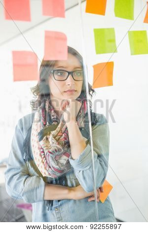 Creative businesswoman reading sticky notes on glass wall in office
