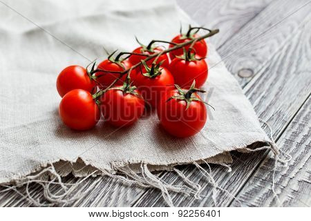 Cherry Tomatoes On A Wooden Surface And Homespun Cloth With Natural Light.