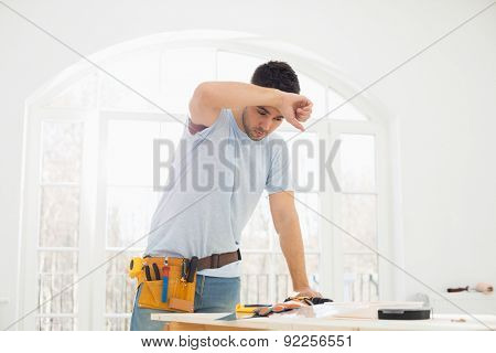 Mid-adult carpenter wiping his brow in new house