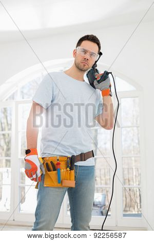 Confident mid-adult man with drill in new house
