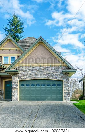 Two-car garage of a luxury house against blue sky.