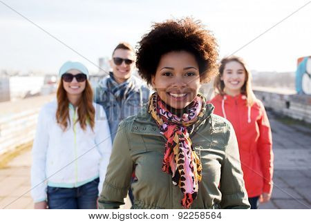 people, friendship and international concept - happy african american young woman or teenage girl in front of her friends on city street