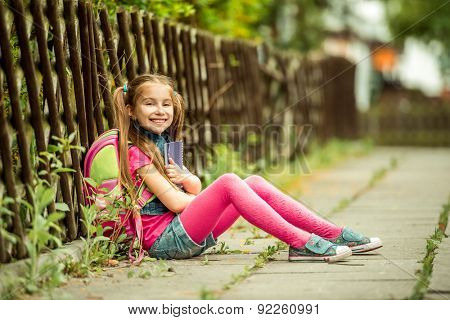 Little pretty schoolgirl reading a book sitting on the street