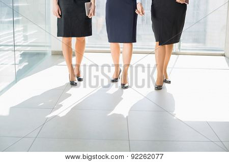 Low section of businesswomen standing on tiled floor in office