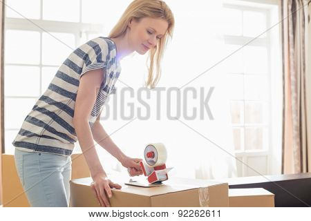 Woman packing moving box at home