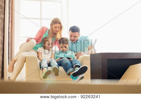 Family looking at boy playing hand-held video game at home