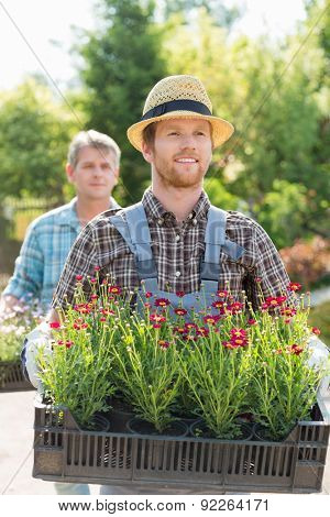 Male gardeners carrying flower pots in crates at plant nursery