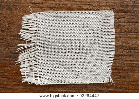 a patch of  fiberglass cloth on a grunge wood background