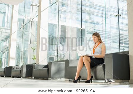 Full-length of businesswoman using laptop at office lobby