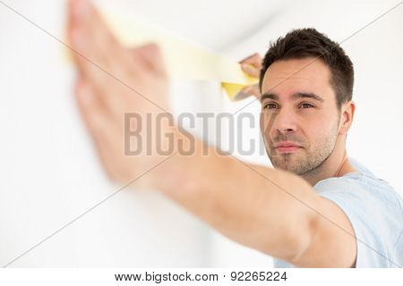 Man applying duct tape on wall