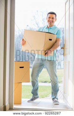 Portrait of happy man carrying cardboard box while entering new home