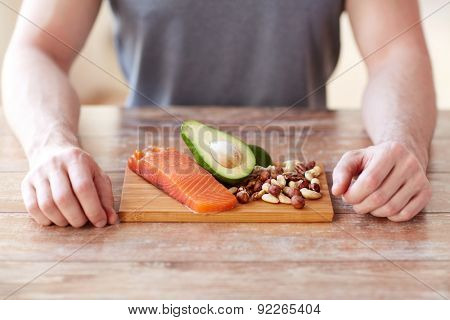 healthy lifestyle, diet and people concept - close up of male hands with food rich in protein on cutting board on table