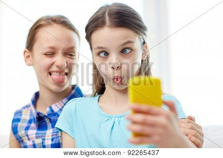 people, children, technology, friends and friendship concept - happy little girls taking selfie with smartphone and having fun at home
