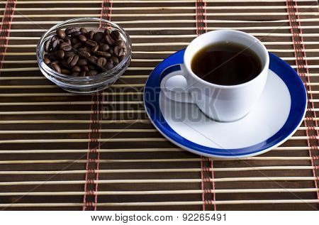 Cup Of Coffee With Coffee Grains On A Saucer