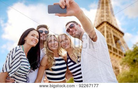 summer, france, tourism, technology and people concept - group of smiling friends taking selfie with smartphone over eiffel tower in paris background