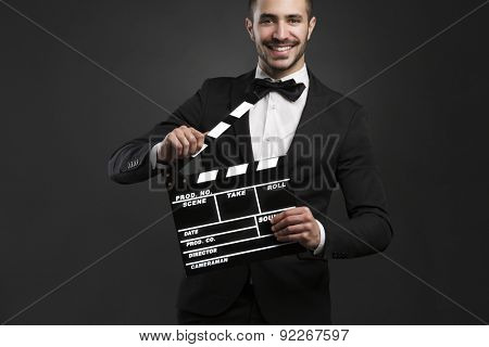 Portrait of a beautiful latin man with tuxedo and holding a clapboard