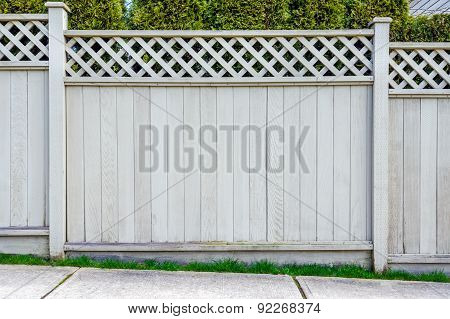 Wooden fence with trees in the background.
