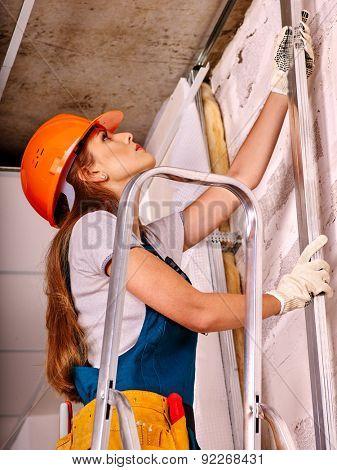 Happy woman in builder uniform and helmet  indoor.