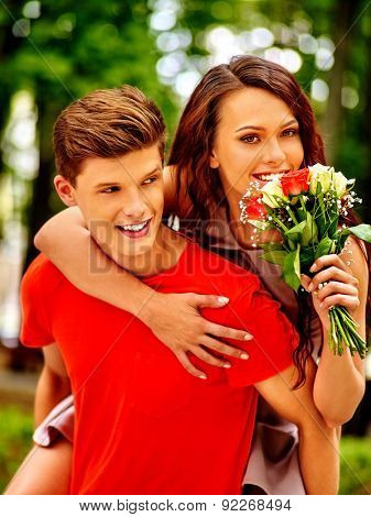 Couple with flower at park. Outside happy first date.
