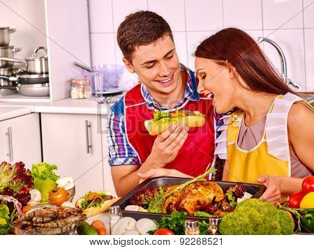 Happy young couple cooking chicken at kitchen indoor.