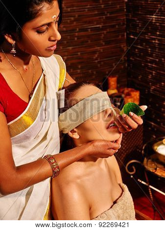 Woman having fresh leaf nose ayurveda spa treatment.