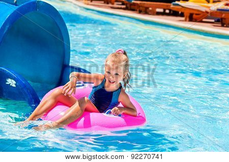 Little girl running with pink inflatable ring.