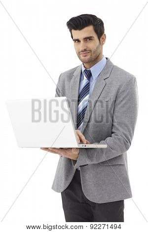 Handsome young businessman standing, working on laptop computer, looking at camera, smiling.
