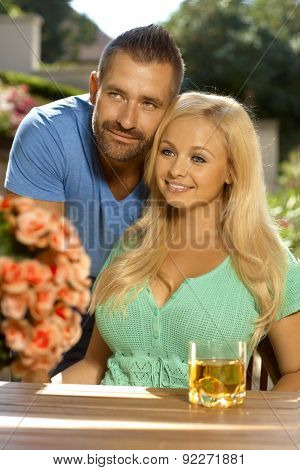 Portrait of romantic young couple sitting at summer garden, outdoors. Attractive, busty blonde woman with cleavage.