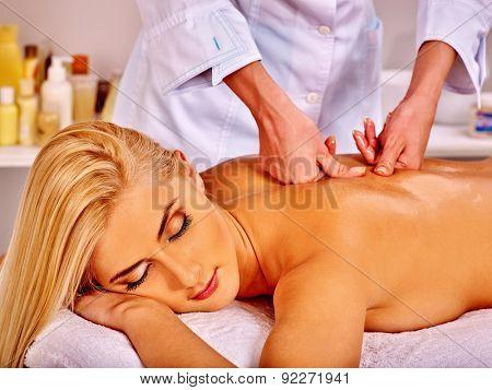 Blond woman getting massage in health resort.