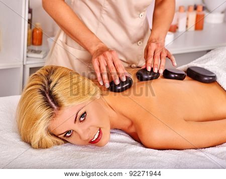 Satisfied woman getting classical stone massage in health resort.