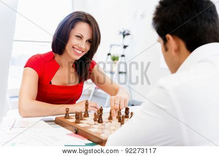 Businesswoman playing chess in office