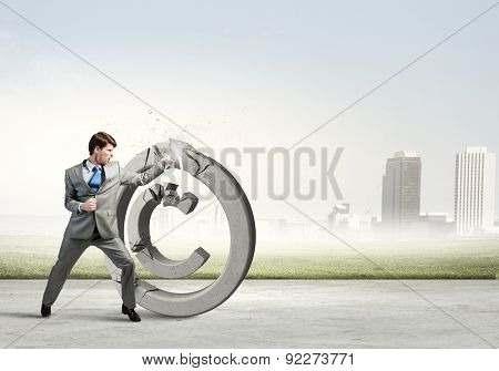 Furious businessman crashing with fist stone copyrighting symbol
