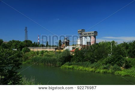 Old factory with silo tanks for corn near river