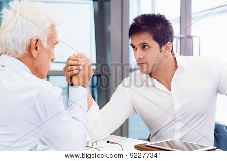 Two businessmen competing arm wrestling in office