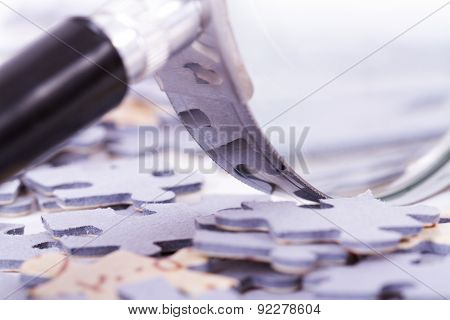 Close Up Magnifying Glass And Puzzle Pieces