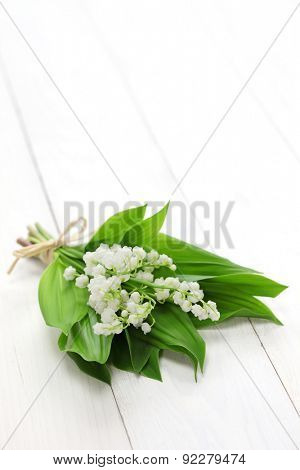 lily of the valley posy isolated on white wooden background