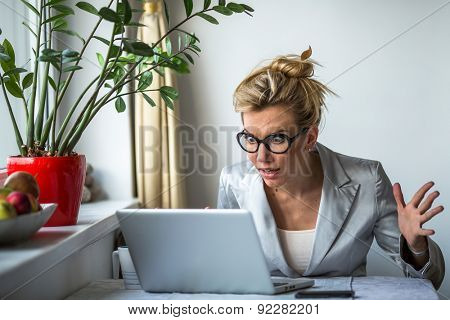 Nervous business woman screaming loudly at her laptop in office. Stress.