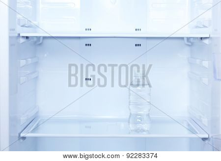Single bottle of water in refrigerator close up