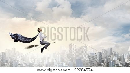 Young businessman flying on broom high in sky